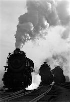 steam engine - 1930s - 1940s HEAD-ON VIEW OF THREE STEAM ENGINES SILHOUETTED AGAINST BILLOWING SMOKE AND STEAM OUTDOOR Stock Photo - Premium Rights-Managednull, Code: 846-05648053