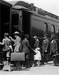 1920s FAMILY MOTHER FATHER SON DAUGHTER BOARDING PASSENGER TRAIN ASSISTED BY TRAINMAN AND PORTERS CARRYING LUGGAGE OUTDOOR