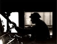 steam engine - 1920s - 1930s - 1940s SILHOUETTE TRAIN ENGINEER AT CONTROLS IN LOCOMOTIVE CAB OF RAILROAD STEAM ENGINE Stock Photo - Premium Rights-Managednull, Code: 846-05648090