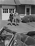 1950s COUPLE CARRYING LUGGAGE WALKING TOWARDS CONVERTIBLE CAR IN DRIVEWAY