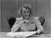 secretary desk - 1930s SERIOUS WORRIED WOMAN AT DESK GOING OVER PAPERS BILLS LOOKING OFF TO SIDE Stock Photo - Premium Rights-Managednull, Code: 846-05648114