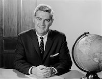1960s SMILING MAN SITTING AT DESK WITH EARTH GLOBE Stock Photo - Premium Rights-Managednull, Code: 846-05648123