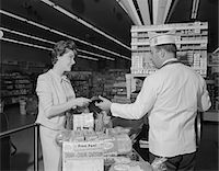 1960s WOMAN PAYING AT GROCERY STORE CHECKOUT MALE CASHIER Stock Photo - Premium Rights-Managednull, Code: 846-05648151