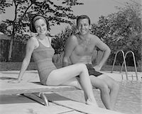 1960s MAN WOMAN COUPLE SITTING ON DIVING BOARD ON SIDE OF SWIMMING POOL Stock Photo - Premium Rights-Managednull, Code: 846-05648202