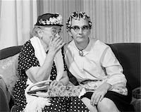 1960s OLDER WOMEN ON COUCH SHARING SECRET ONE IN FLOWERED HAT ONE IN HAIR CURLERS Stock Photo - Premium Rights-Managednull, Code: 846-05648208