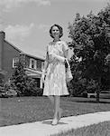 1960s WOMAN WEARING PRINT DRESS HOLDING HANDBAG WALKING DOWN SUBURBAN STREET Stock Photo - Premium Rights-Managed, Artist: ClassicStock, Code: 846-05648216