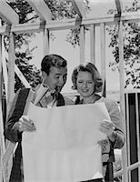 1960s COUPLE LOOKING AT HOUSE PLANS BLUEPRINTS MAN SMOKING PIPE Stock Photo - Premium Rights-Managednull, Code: 846-05648218