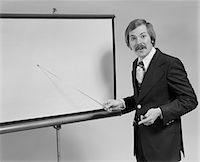 1970s YOUNG MAN SPEAKING POINTING TO BLANK SLIDE SCREEN FOR PRESENTATION Stock Photo - Premium Rights-Managednull, Code: 846-05648290