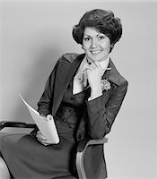1970s SMILING WOMAN SITTING IN OFFICE CHAIR HOLDING PAPERS Stock Photo - Premium Rights-Managednull, Code: 846-05648293