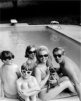 1960s - 1970s FAMILY PORTRAIT FATHER MOTHER SONS DAUGHTER SWIMMING POOL SIDE WITH DACHSHUND DOG ALL WEARING SUNGLASSES Stock Photo - Premium Rights-Managednull, Code: 846-05648302