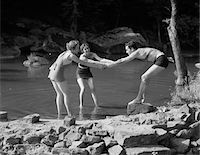 1920s - 1930s TWO WOMEN PULLING MAN INTO WOODLAND SWIMMING POND ALL WEARING BATHING SUITS Stock Photo - Premium Rights-Managednull, Code: 846-05648331