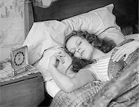 1930s WOMAN SLEEPING ASLEEP IN BED ALARM CLOCK ON NIGHT TABLE Stock Photo - Premium Rights-Managednull, Code: 846-05648338