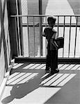 1950s SCHOOLBOY WITH BOOKS UNDER ARM LOOKING OUT WINDOW BETWEEN BARS OF RAILING SHADOW CAST BEHIND HIM