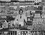 1940s SMILING MAN GROCER STANDING BEHIND COUNTER FILLED WITH VARIOUS FOOD PRODUCTS IN CANS AND PACKAGES INDOOR GROCERY STORE Stock Photo - Premium Rights-Managed, Artist: ClassicStock, Code: 846-05648367