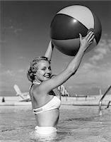 1950s SIDE VIEW OF BLONDE IN WHITE BIKINI STANDING IN POOL IN WAIST-HIGH WATER HOLDING BEACH BALL IN AIR Stock Photo - Premium Rights-Managednull, Code: 846-05648406
