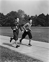 1930s - 1940s TWO SMILING BOYS RUNNING CARRYING SCHOOL BOOKS Stock Photo - Premium Rights-Managednull, Code: 846-05648411