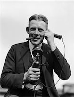 1920s PORTRAIT OF BUSINESSMAN TALKING ON CANDLESTICK PHONE SMOKING CIGAR OFFICE INDOOR Stock Photo - Premium Rights-Managednull, Code: 846-05648432