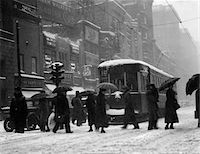 1920s - 1930s CROWD CARRYING UMBRELLAS CROSSING STREET IN FRONT OF STREET CAR TROLLEY DURING SNOWSTORM Stock Photo - Premium Rights-Managednull, Code: 846-05648436
