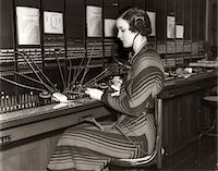 switchboard operator - 1930s WOMAN TELEPHONE OPERATOR SITTING AT LARGE MANUAL SWITCHBOARD DIRECTING CALLS Stock Photo - Premium Rights-Managednull, Code: 846-05648439
