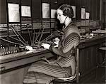 1930s WOMAN TELEPHONE OPERATOR SITTING AT LARGE MANUAL SWITCHBOARD DIRECTING CALLS Stock Photo - Premium Rights-Managed, Artist: ClassicStock, Code: 846-05648439