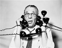 extremism - 1950s - 1960s PORTRAIT OF FRAZZLED BUSINESSMAN TRYING TO ANSWER FOUR BLACK TELEPHONES PHONES AT ONCE Stock Photo - Premium Rights-Managednull, Code: 846-05648445