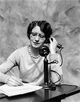 right - 1920s WOMAN WEARING PINCE-NEZ GLASSES SITTING AT DESK TALKING ON CANDLESTICK PHONE AND WRITING Stock Photo - Premium Rights-Managednull, Code: 846-05648449