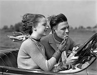 1930s MAN DRIVING CONVERTIBLE AUTOMOBILE WHILE GIRLFRIEND LIGHTS HIS CIGARETTE Stock Photo - Premium Rights-Managednull, Code: 846-05648459