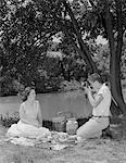 1950s TEENAGE COUPLE PICNIC BOY TAKING PHOTOGRAPH OF GIRL OUTDOORS