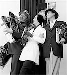 1950s JOYOUS LAUGHING WOMAN AND TWO MEN CARRYING CHRISTMAS GIFTS