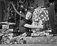 sitting under tree - 1950s WOMAN SITTING BY CHRISTMAS TREE HUGGING PILE OF PRESENTS Stock Photo - Premium Rights-Managednull, Code: 846-05648536