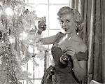 1950s WOMAN IN PARTY DRESS DECORATING INDOOR CHRISTMAS TREE HANGING BALLS ON BRANCH SMILING