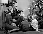 1960s FAMILY FATHER MOTHER TWO SONS SMILING SITTING BY CHRISTMAS TREE IN LIVING ROOM READING A BOOK