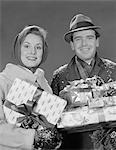 1960s COUPLE MAN AND WOMAN HOLDING WRAPPED CHRISTMAS PRESENTS AND PACKAGES