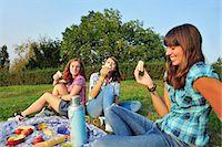 Teenage girls picnicking in rural field Stock Photo - Premium Royalty-Freenull, Code: 649-05648922