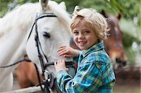 Smiling boy petting horse in yard Stock Photo - Premium Royalty-Freenull, Code: 649-05649029