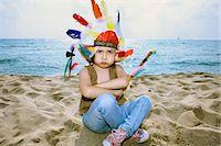 Toddler in Indian headdress on beach Stock Photo - Premium Royalty-Freenull, Code: 649-05649346