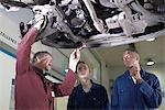 Teacher helping students with car engine Stock Photo - Premium Royalty-Free, Artist: Blend Images, Code: 649-05649536