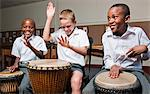 Three boys playing wooden hand drums in classroom, Johannesburg, Gauteng Province, South Africa Stock Photo - Premium Royalty-Free, Artist: Ed Gifford, Code: 682-05649935