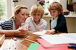 Mother helping older son with homework at the kitchen table Stock Photo - Premium Royalty-Freenull, Code: 614-05650647