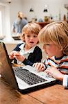 Young boy using laptop with his younger brother looking across at the monitor Stock Photo - Premium Royalty-Freenull, Code: 614-05650651
