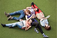 Four people lying down with a laptop, digital tablet and mobile phone Stock Photo - Premium Royalty-Freenull, Code: 614-05650686