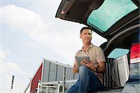 Man using data tablet in airport carpark Stock Photo - Premium Royalty-Freenull, Code: 614-05650827