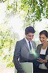 Business people looking at report together outdoors Stock Photo - Premium Royalty-Freenull, Code: 635-05651413