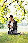Businesswoman sitting in grass text messaging on cell phone