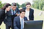 Business people using computer together outdoors Stock Photo - Premium Royalty-Free, Artist: Eyecandy Pro, Code: 635-05651432