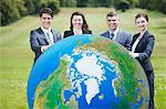 Business people standing in field with large ball