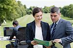 Business people looking at report together outdoors Stock Photo - Premium Royalty-Free, Artist: Ikon Images, Code: 635-05651458
