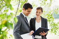 Business people looking at report together outdoors Stock Photo - Premium Royalty-Freenull, Code: 635-05651468