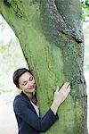 Businesswoman hugging tree Stock Photo - Premium Royalty-Freenull, Code: 635-05651471