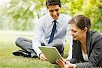 Business people using digital tablet together outdoors Stock Photo - Premium Royalty-Free, Artist: Blend Images, Code: 635-05651477